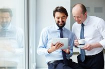 Image of young businessman holding touchpad while explaining idea to his colleague at meeting